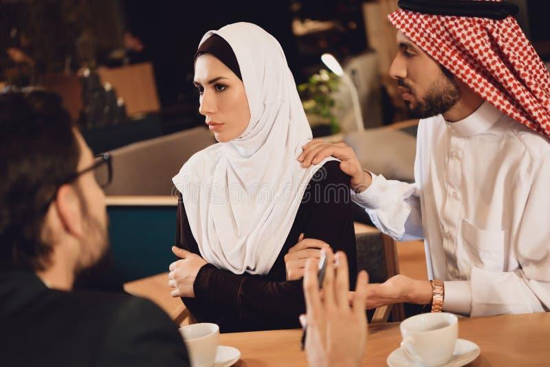 Арабский супруг извиняется к жене на приеме стоковое фото rf