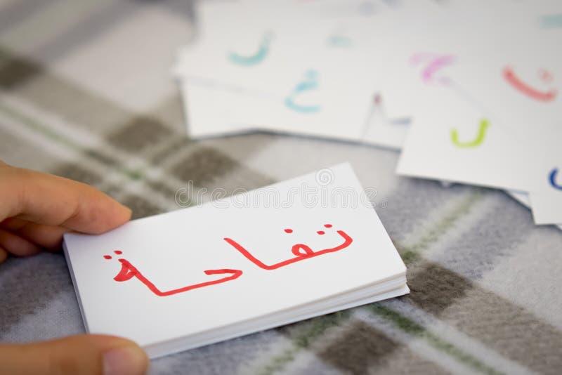 Арабский; Учить новое слово с карточками алфавита; Запись a стоковые фото