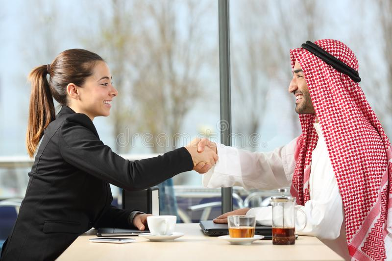 Арабский handshaking бизнесмена и коммерсантки стоковое изображение rf