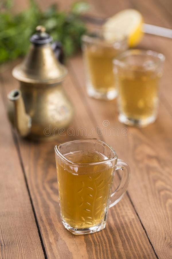 Арабское стекло чая мяты и лимона с чайником на деревянном столе стоковые изображения rf