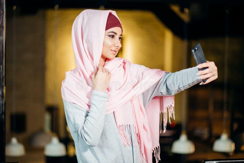 Аравийская мусульманская женщина принимая selfie с телефоном в кафе стоковые изображения rf