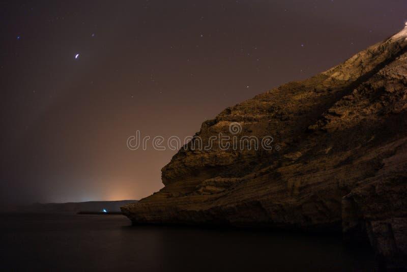 Аравийская ноча на море Омана, с отражениями, играет главные роли стоковая фотография