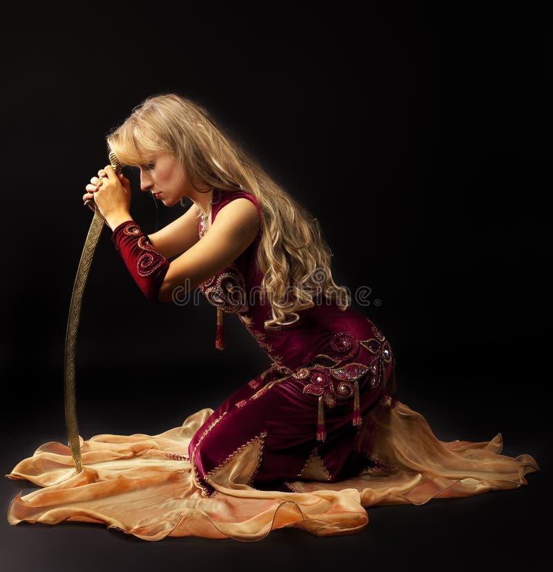 аравийская тоскливость saber costume сидит женщина стоковая фотография
