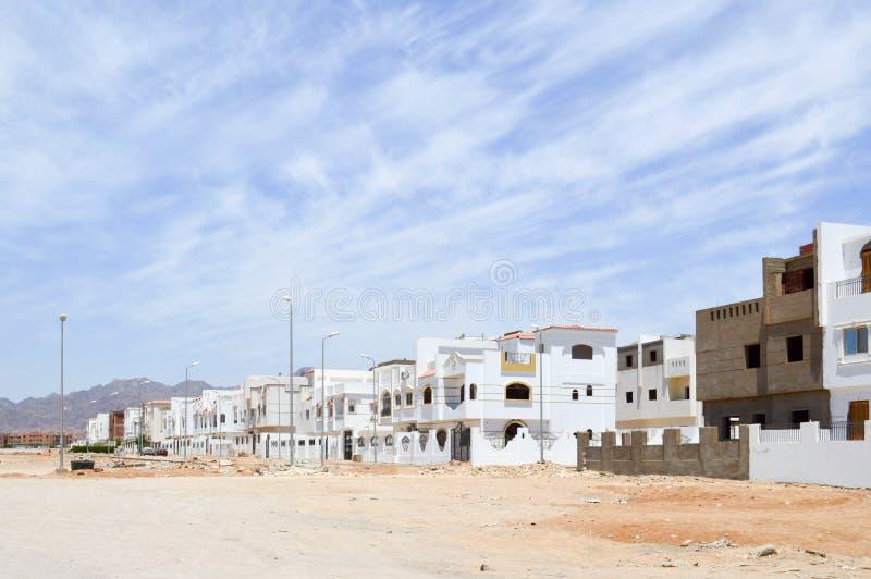 Аравийские прямоугольные и квадратные центры города, дома в пустыне с окнами на фоне желтого песка и красивый bl стоковое фото rf