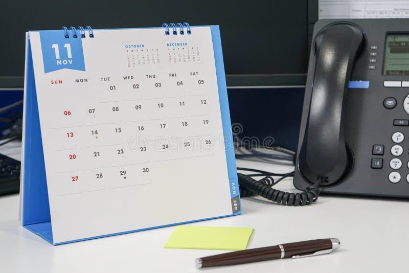 Аранжируйте встречу в ноябре на календаре с обсуждением телефона стоковые изображения rf