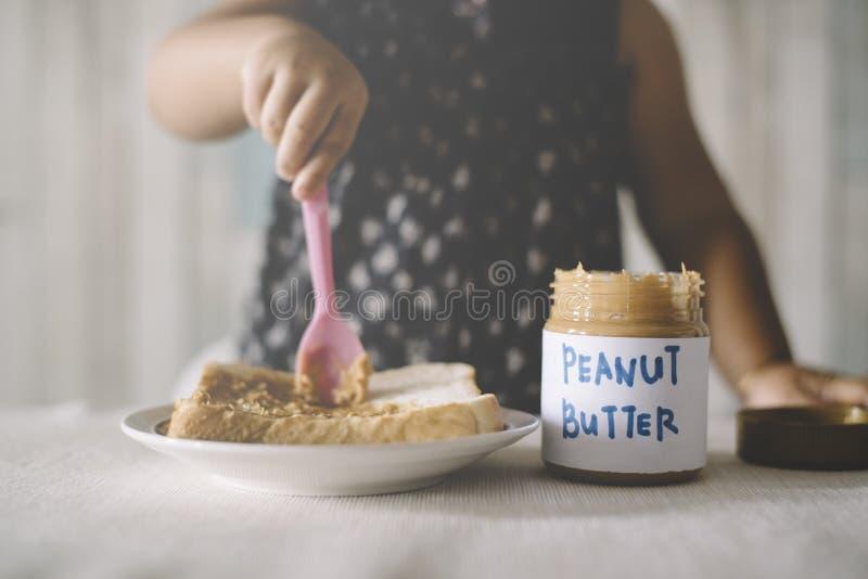 Арахисовое масло азиатского ребёнка играя/распространяя на хлебе стоковое изображение