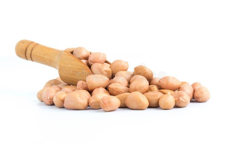 арахисы в деревянной ложке изолированной на белизне стоковое изображение