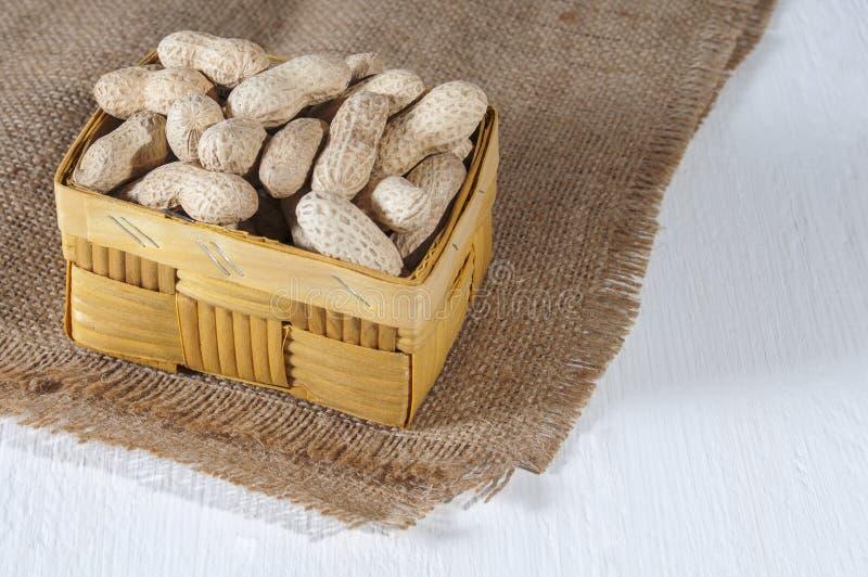 Арахисы в плетеной корзине на мешковине деревянное предпосылки белое Здоровая еда и здравоохранение стоковая фотография