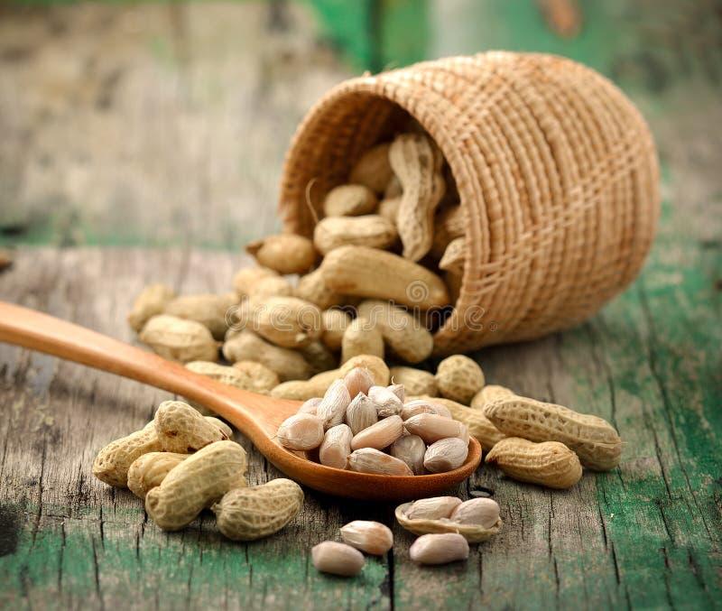 Арахисы в woodspoon и корзине на древесине стоковое фото