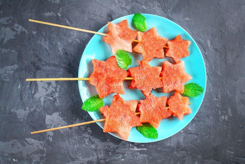 Арбуз в форме звезд на протыкальниках с листьями мяты лежит на плите Голубое блюдо как ракета в космосе Взгляд сверху стоковая фотография