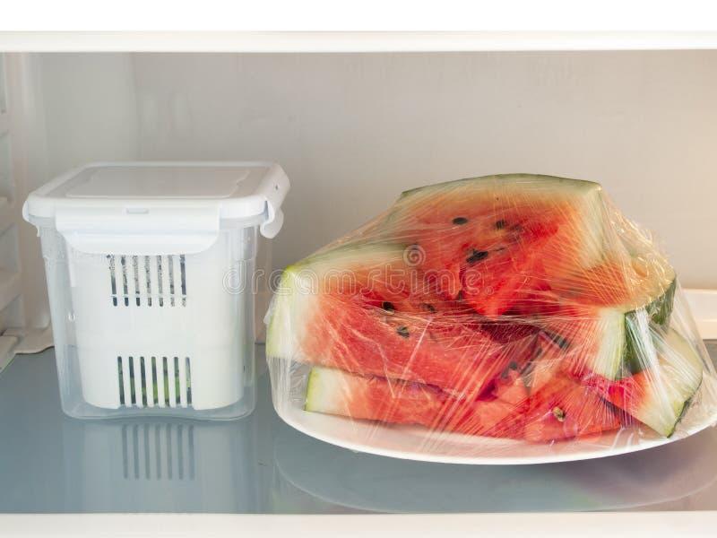 Арбуз в холодильнике фильма простирания покрытом стоковые фотографии rf