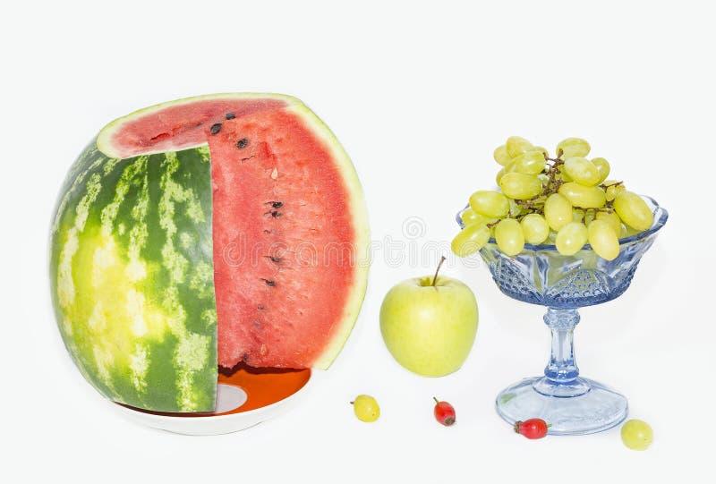 Арбуз, яблоко и виноградины в вазе стоковое фото