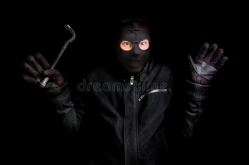 Арестованный похититель в балаклаве с ломом и поднятыми оружиями стоковые изображения