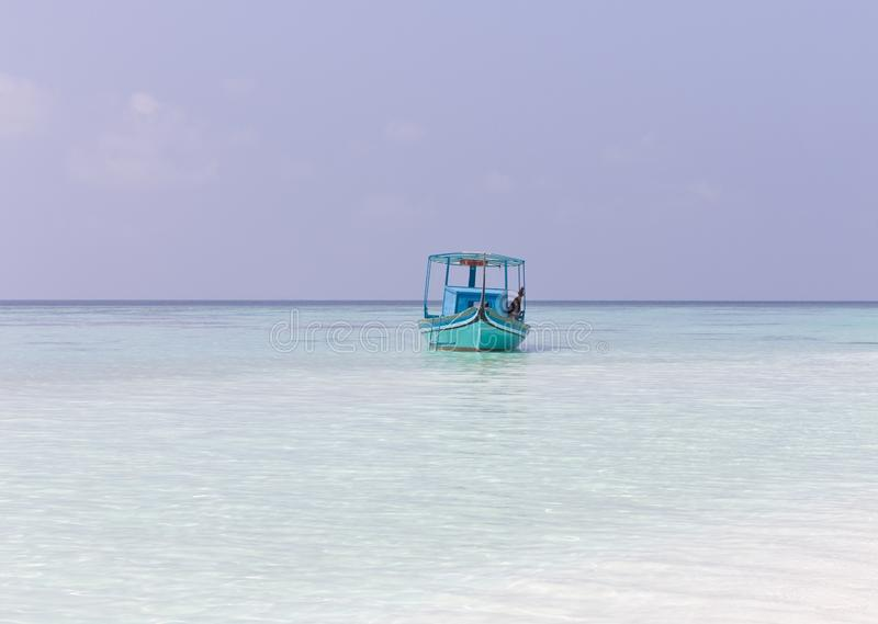 Ари Атолл, Мальдивы: Мальдивский парус рыбачит на своей синей лодке под названием 'dhoni' стоковая фотография rf