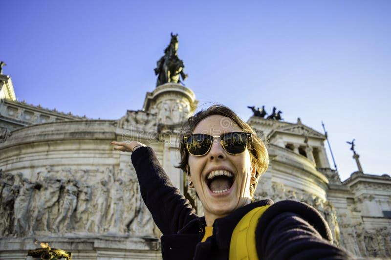 Аркада Venezia, Roma, Италия Счастливая усмехаясь молодая женщина принимая selfie с фронтом памятника Виктор Emmanuel II в b стоковая фотография rf