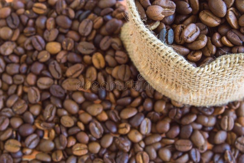 Ароматичные кофейные зерна в мешке и вокруг стоковые изображения rf