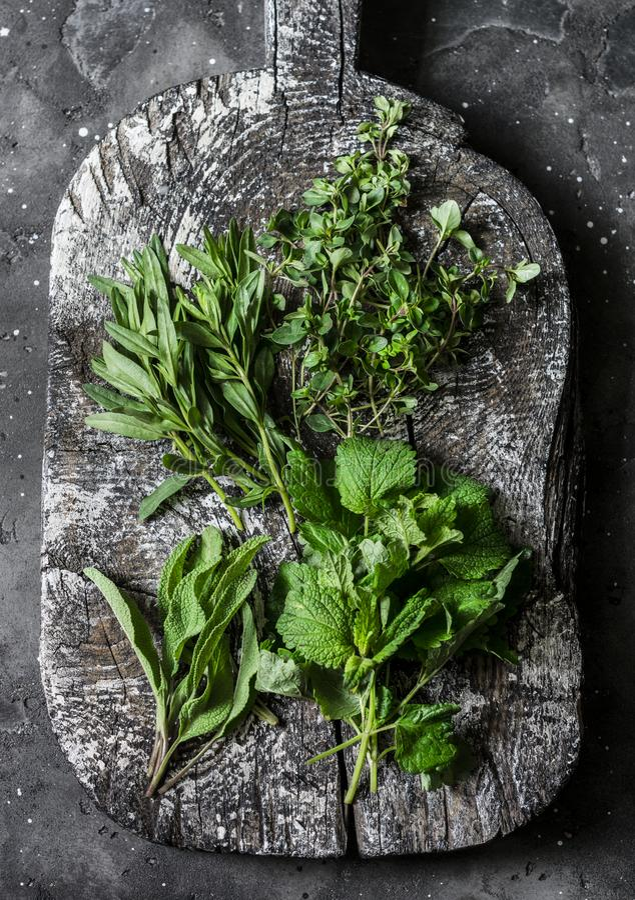 Ароматичные травы сада, пищевые ингредиенты, приправы - шалфей, тимиан, мята, астрагон на деревянной деревенской прерывая доске н стоковые изображения rf