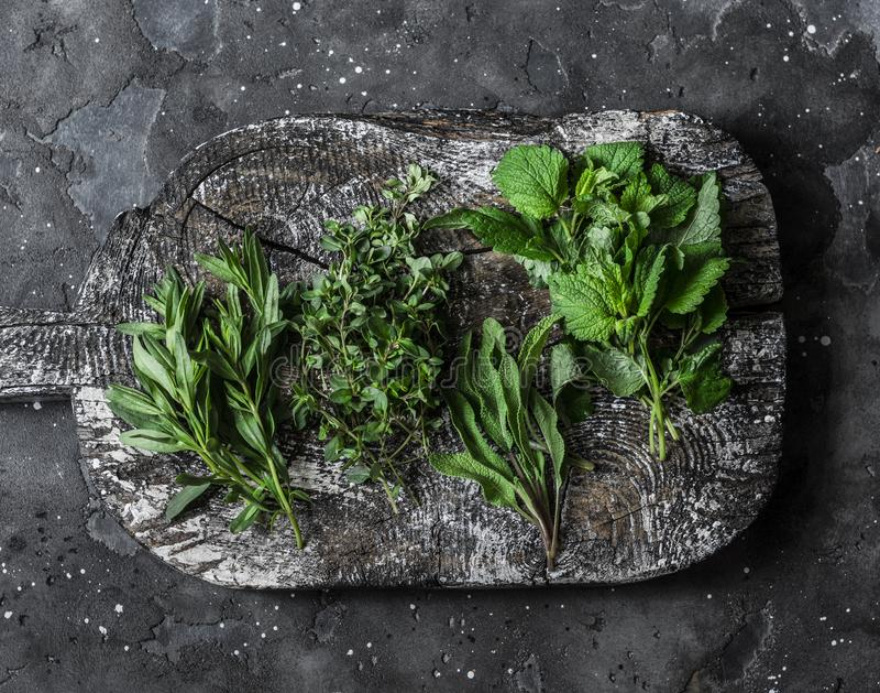 Ароматичные травы сада, пищевые ингредиенты, приправы - шалфей, тимиан, мята, астрагон на деревянной деревенской прерывая доске н стоковые фотографии rf