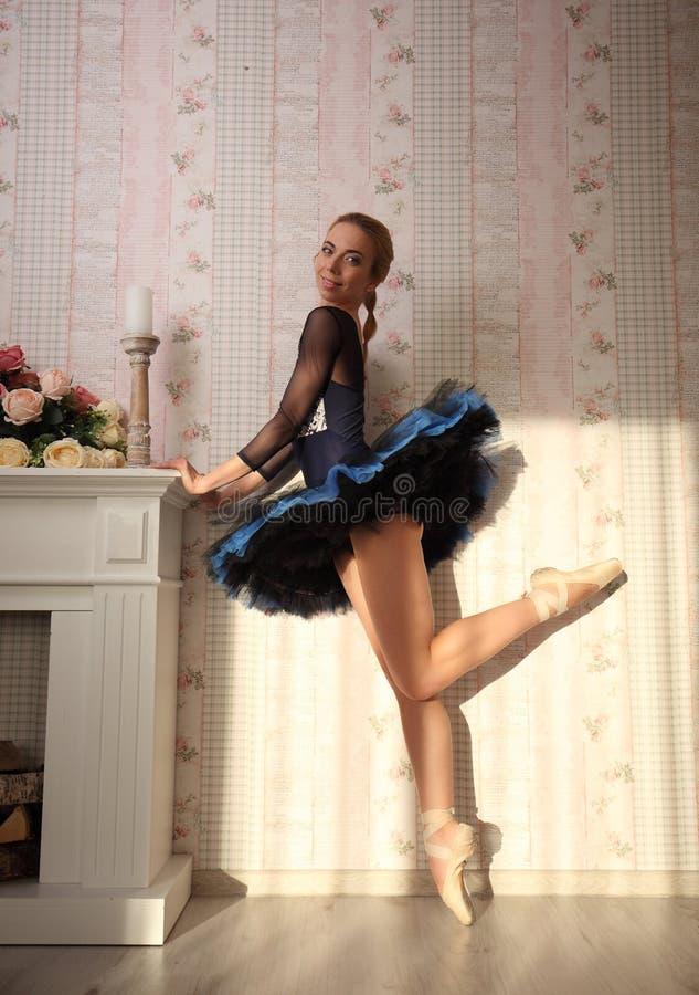 Артист балета в свете солнца в домашнем интерьере, стоя на одной ноге стоковое фото