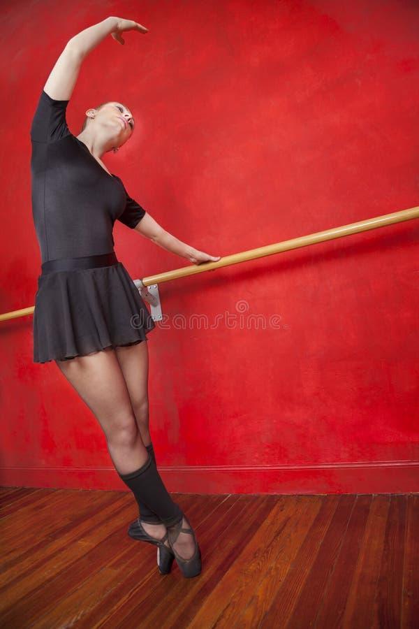 Артист балета практикуя на Barre в студии стоковые фотографии rf