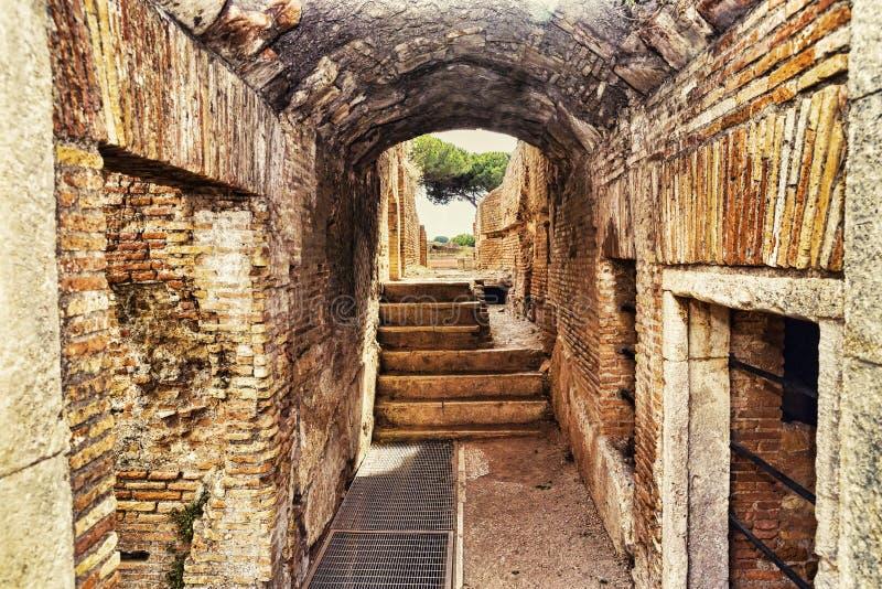 Археологические раскопки Ostia Antica: Внутри руин с сводом и вымощенной дорогой стоковая фотография rf