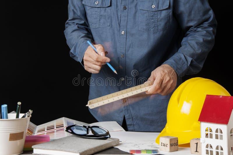 Архитекторы, инженер, дизайн интерьера выбирают материалы цвета конструируют построить здание на столе в офисе Конструкция и стоковое фото rf