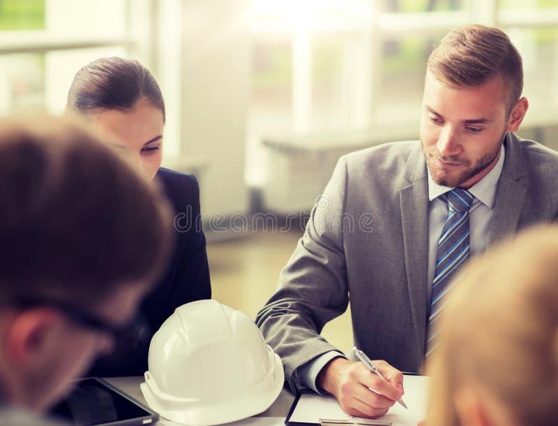 Архитекторы со шлемом и доской сзажимом для бумаги на офисе стоковая фотография
