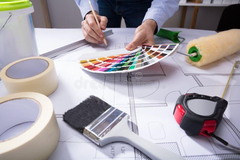 Архитектор используя образец гида цвета пока рисующ светокопию стоковые изображения rf