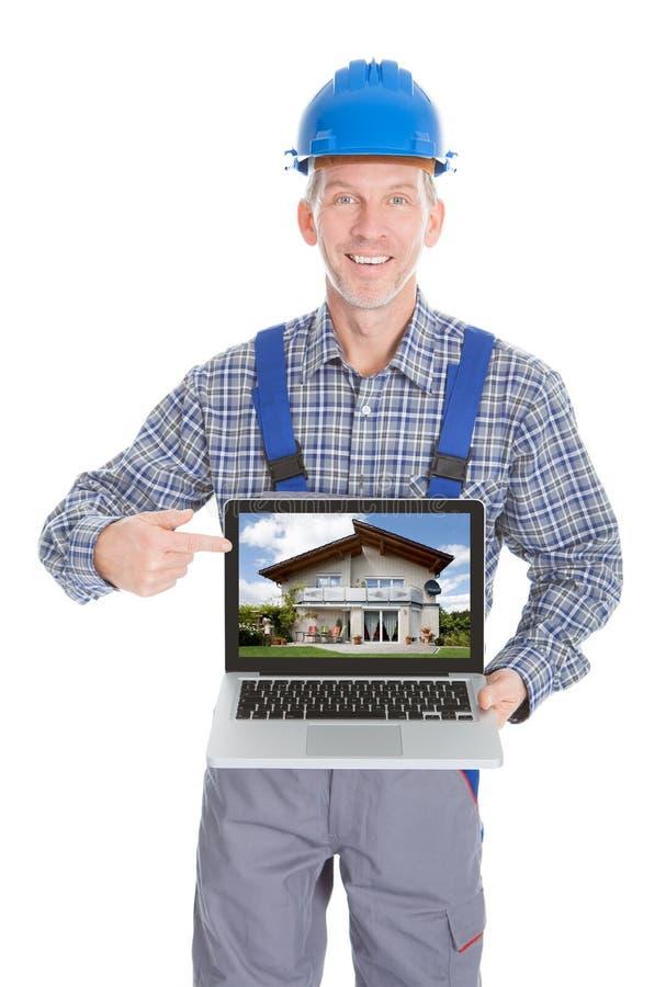 Архитектор показывая изображение дома на компьтер-книжке стоковые изображения