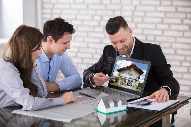 Архитектор показывая модель дома к парам в офисе стоковая фотография rf