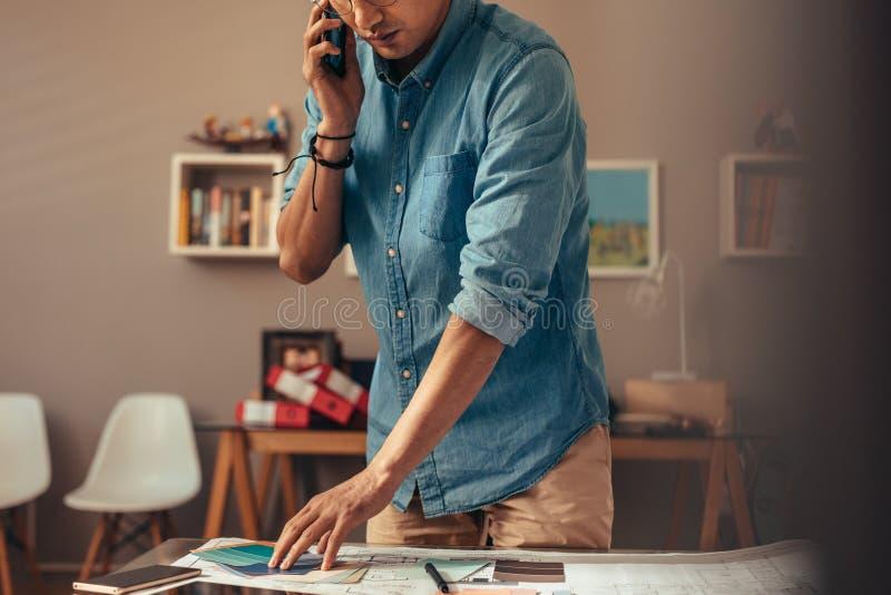 Архитектор разговаривая с клиентом над телефоном для выборов цвета стоковые изображения
