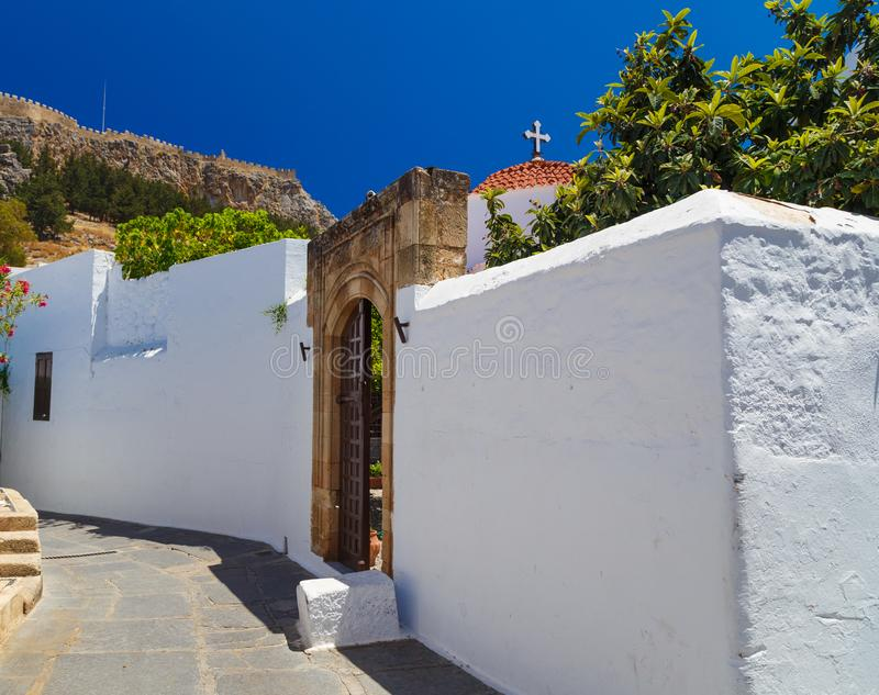 Архитектура древнегреческого с традиционными дверями и декоративной мостовой в городке Lindos, острове Родоса, Греции стоковая фотография rf
