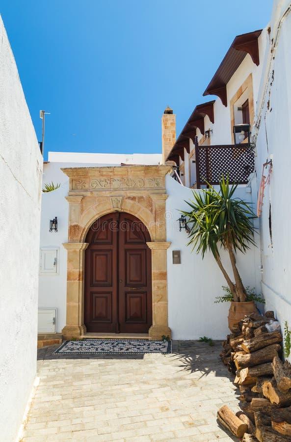 Архитектура древнегреческого с традиционными дверями и декоративной мостовой в городке Lindos, острове Родоса, Греции, Европе стоковая фотография