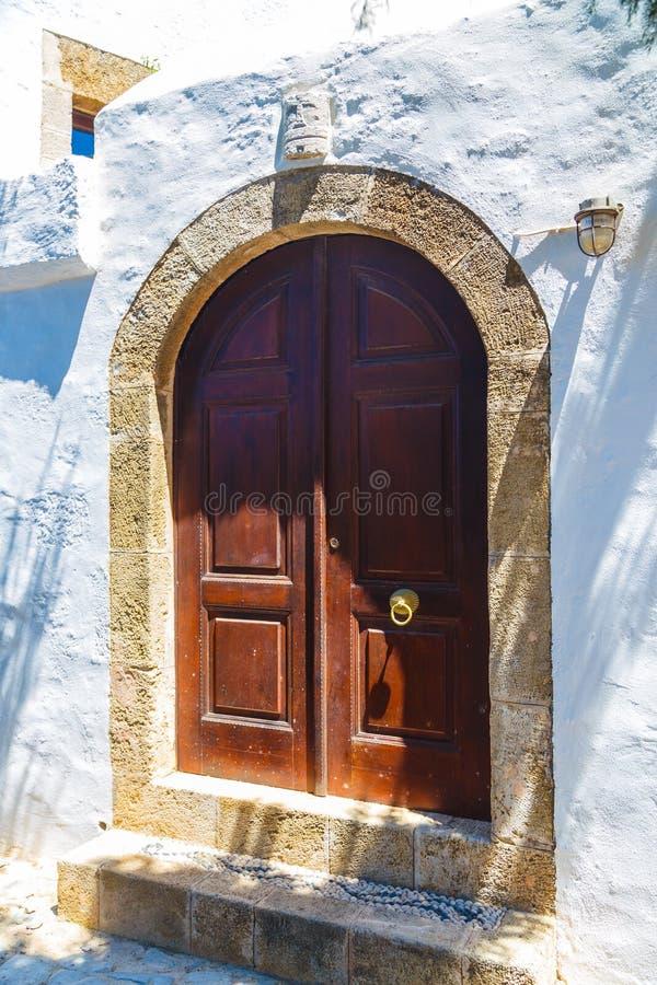 Архитектура древнегреческого с традиционными дверями и декоративной мостовой в городке Lindos, острове Родоса, Греции, Европе стоковые фотографии rf