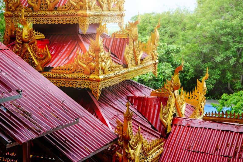 Архитектурноакустическая деталь красочных крыш красного цвета и золота на виске стоковое изображение