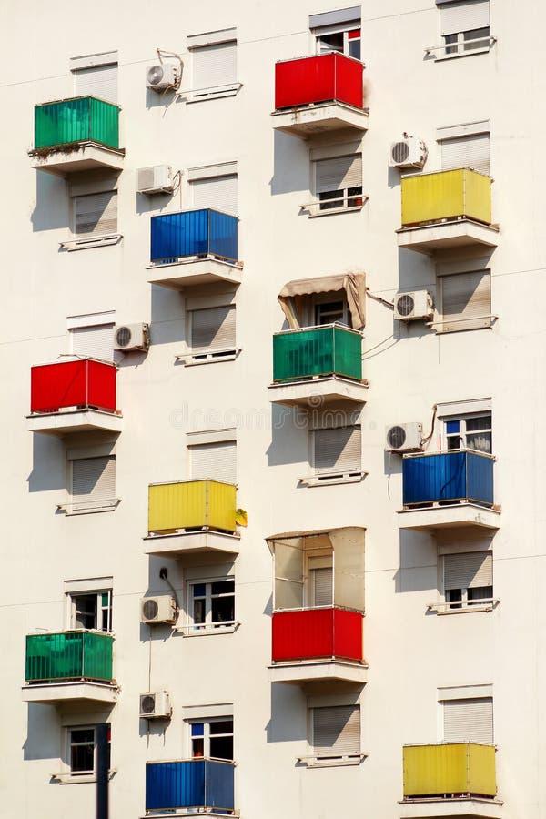 Архитектурноакустические деталь и картина современного жилого дома с красочными балконами и окна квартир стоковые изображения