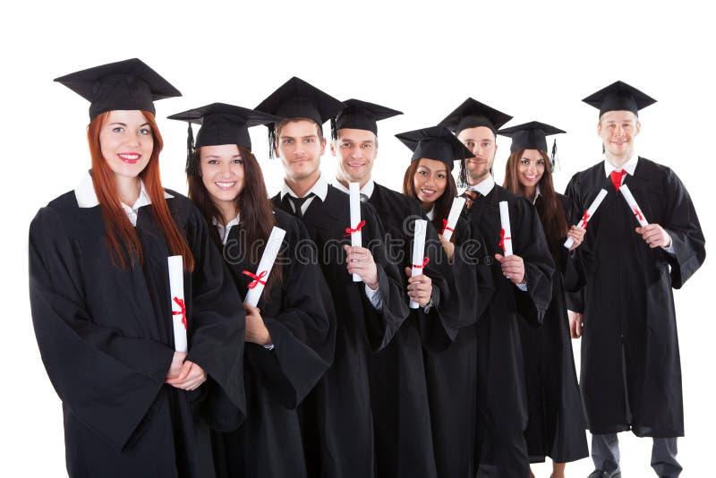 Аспиранты стоя в строке держа дипломы стоковое фото