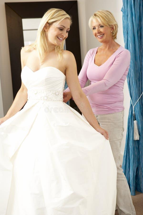 ассистентские сбывания платья невесты пробуя венчание стоковое фото rf
