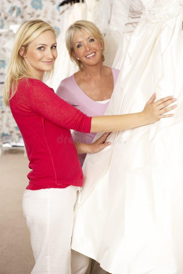 ассистентские сбывания платья невесты пробуя венчание стоковые фото