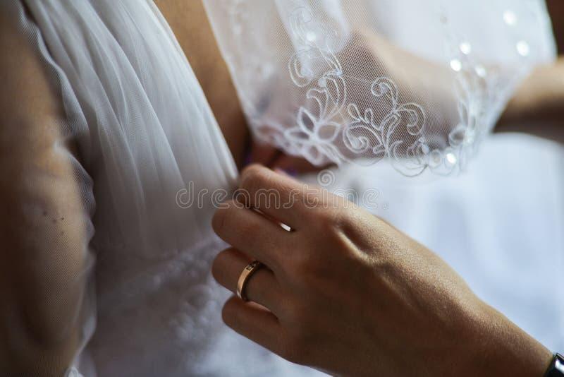 ассистентские сбывания платья невесты пробуя венчание стоковые изображения