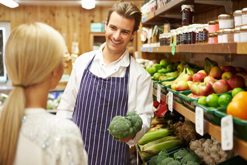Ассистентский клиент порции на Vegetable счетчике магазина фермы стоковое изображение rf