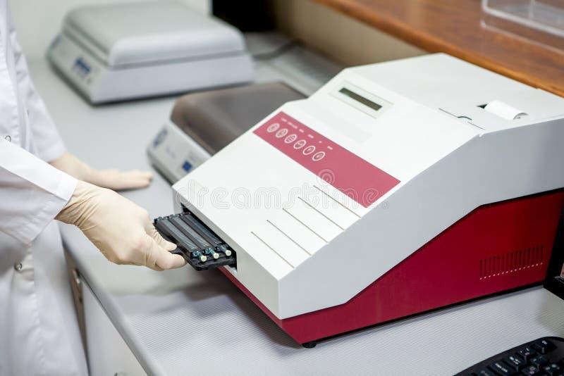 Ассистент лаборатории нагружает образцы в прибор для анализа, конца-вверх стоковое фото rf