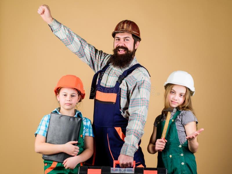 Ассистент рабочий-строителя Построитель или плотник Бородатый человек с маленькими девочками o Творческие способности детей стоковое фото rf