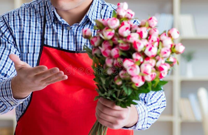 Ассистент цветочного магазина предлагая пук цветков стоковые изображения