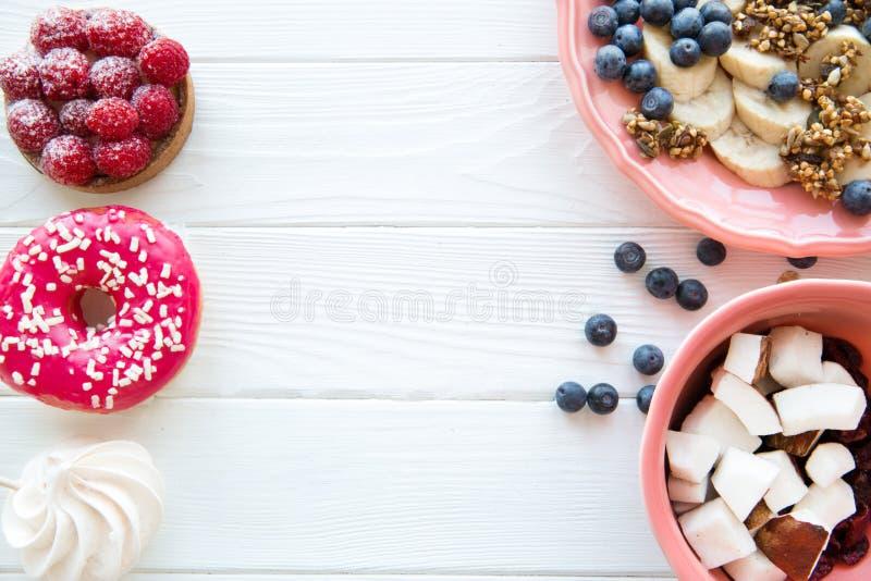 Ассортимент здоровых и нездоровых помадок и десертов, космоса для текста, белой таблицы стоковое фото rf
