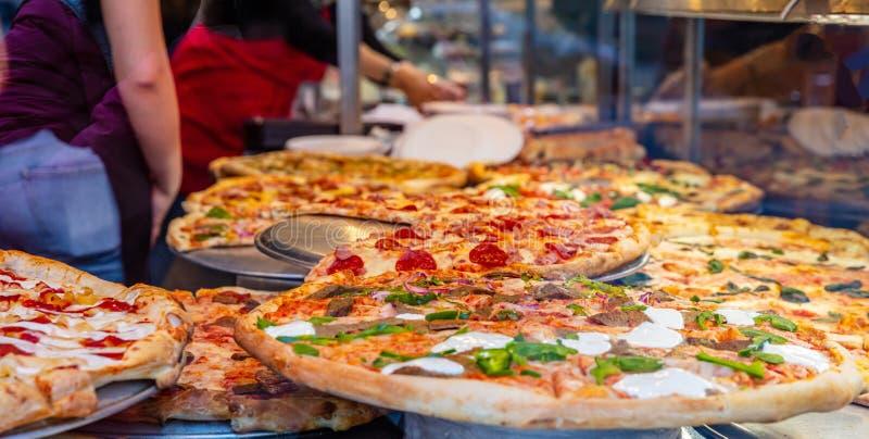 Ассортимент итальянских пицц в дисплее магазина Женские работники служа пиццы стоковые фото