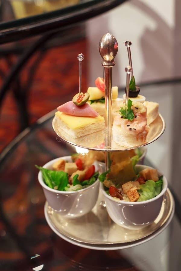 Ассортимент канапе на серебряном подносе на предпосылке таблицы Шведский стол ресторанного обслуживания еды ресторана места гости стоковая фотография