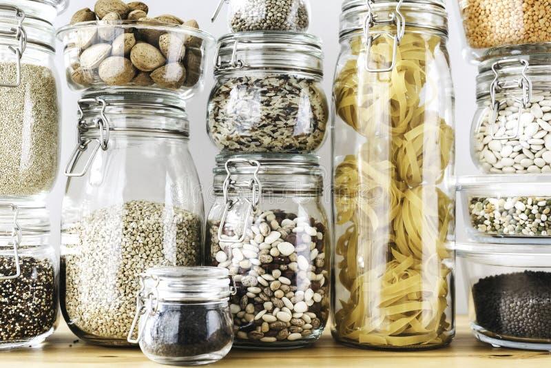 Ассортимент сырых зерен, хлопьев и макаронных изделий в стеклянных опарниках на деревянном столе Здоровый варить, очищает еду, ну стоковые изображения rf