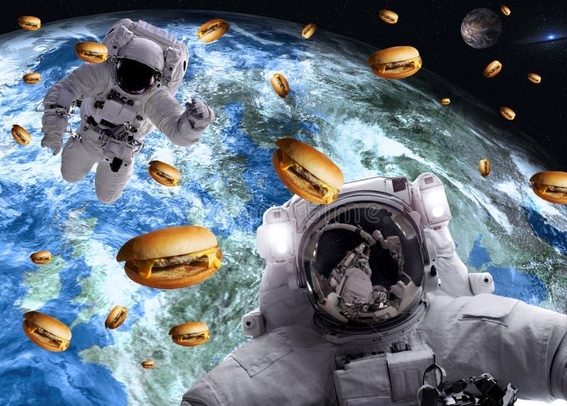 Астронавты в космическом пространстве с cheseburgers на планетах земли и рыноков на предпосылке стоковое фото