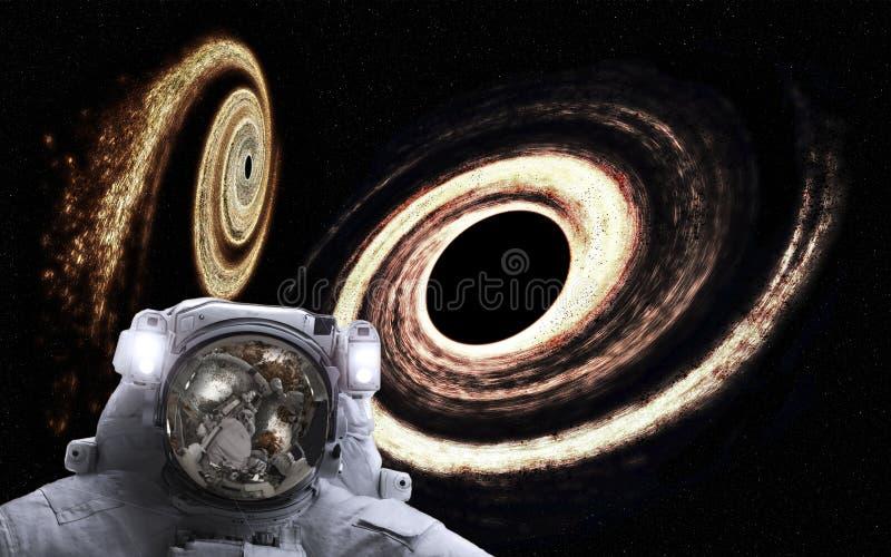 Астронавт в космосе с оранжевыми гигантскими черными дырами позади Элементы этого изображения поставленные NASA стоковые изображения